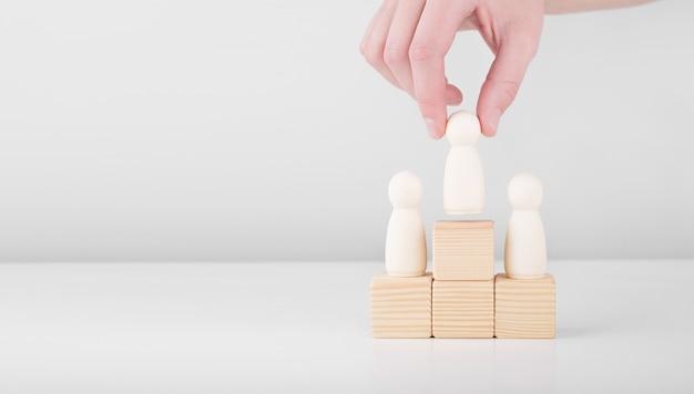 Homem de negócios segurando um homem de madeira que representa o líder aumenta o sucesso ficando no pedestal