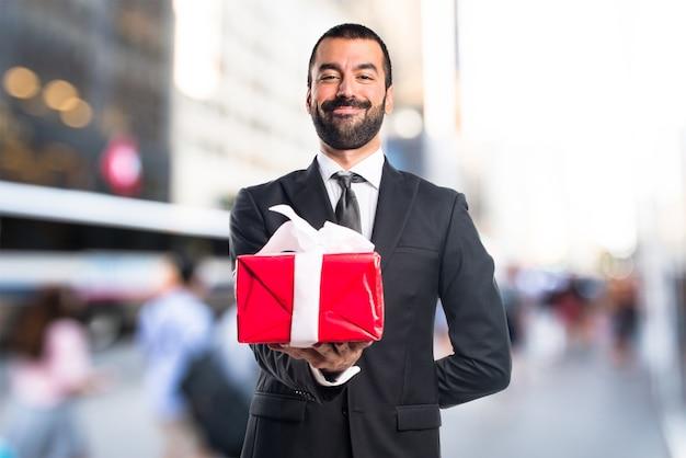 Homem de negócios segurando um presente em um fundo sem foco