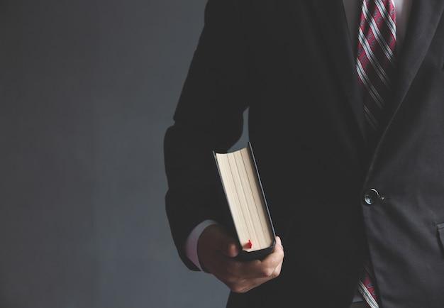 Homem de negócios, segurando uma bíblia no local de trabalho.