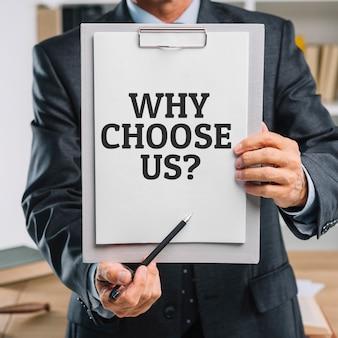 Homem de negócios segurando uma prancheta com a pergunta por que nos escolher