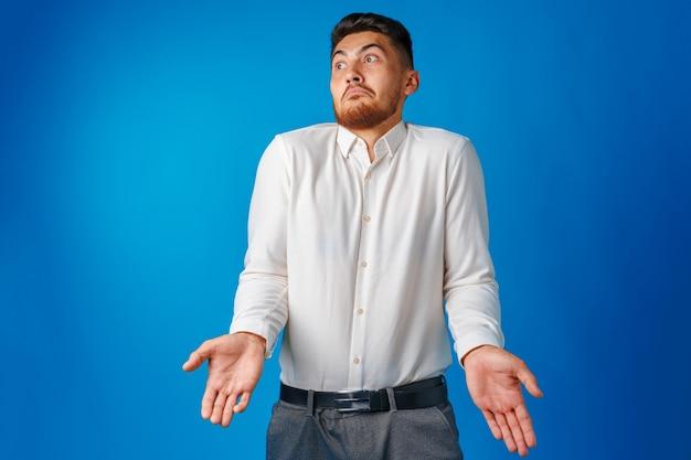 Homem de negócios sem noção gesticulando que não sabe contra o retrato de superfície azul
