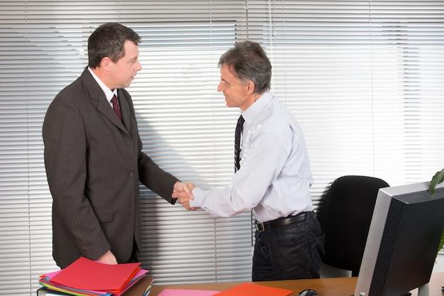 Homem de negócios sênior agita as mãos com seu cliente homem de terno em sua mesa
