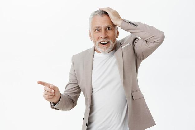 Homem de negócios sênior animado e impressionado apontando o dedo para a esquerda