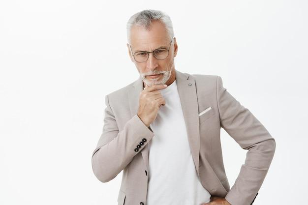 Homem de negócios sênior atencioso tomando decisões, pensando ou ponderando
