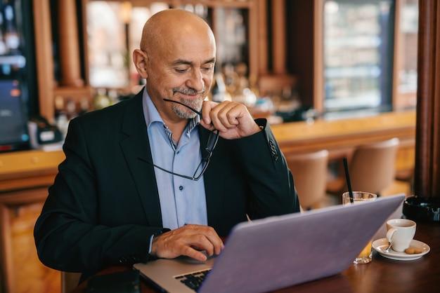 Homem de negócios sênior barbudo de terno segurando óculos na mão e sorrindo enquanto estiver usando o laptop na cafeteria.