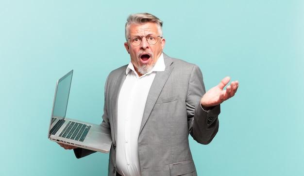 Homem de negócios sênior boquiaberto e surpreso, chocado e surpreso com uma surpresa inacreditável