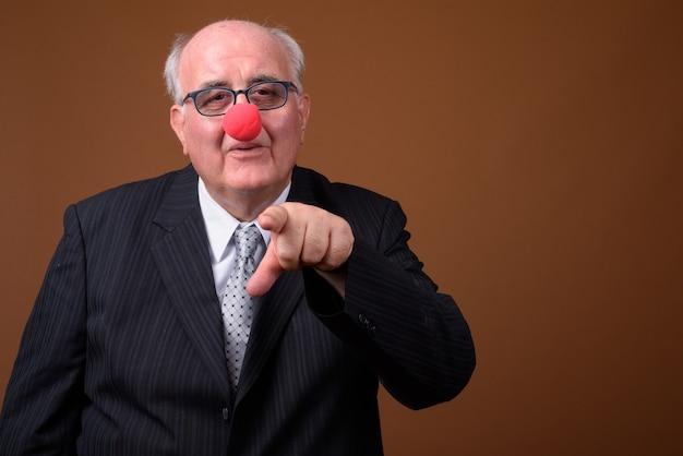 Homem de negócios sênior com excesso de peso usando nariz de palhaço vermelho