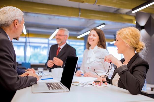 Homem de negócios sênior com laptop sentado junto com o colega no escritório