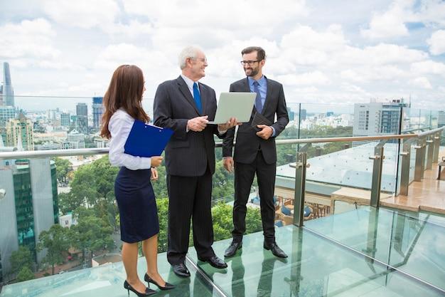 Homem de negócios sênior com um laptop falando com outros dois trabalhadores