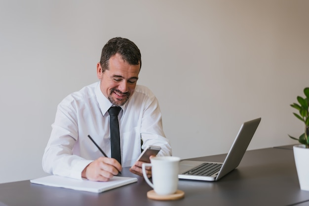 Homem de negócios sênior considerável feliz que usa um smartphone e notas na mesa de escritório.