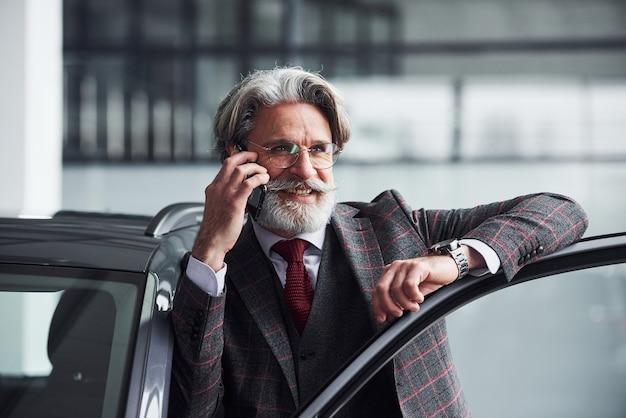 Homem de negócios sênior de terno e gravata com barba e cabelos grisalhos está perto do carro, falando ao telefone e sorrindo.