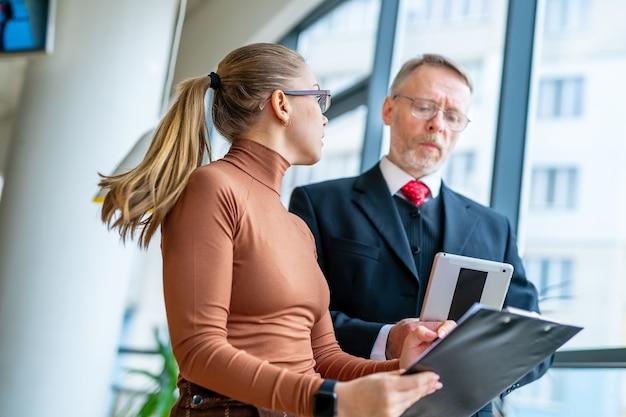 Homem de negócios sênior discutindo ideias de negócios com a ajuda. homem maduro e mulher de negócios em um escritório. vídeo do almoço de negócios