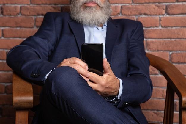 Homem de negócios sênior em terno e aplicação de consultoria de barba branca no telefone no escritório, foto das mãos de um homem usando smartphone nas costas de um empresário.