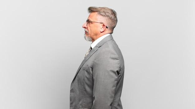 Homem de negócios sênior em vista de perfil, olhando para copiar o espaço à frente, pensando, imaginando ou sonhando acordado