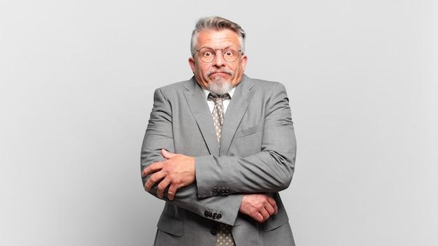 Homem de negócios sênior encolhendo os ombros, sentindo-se confuso e inseguro, duvidando com os braços cruzados e olhar perplexo