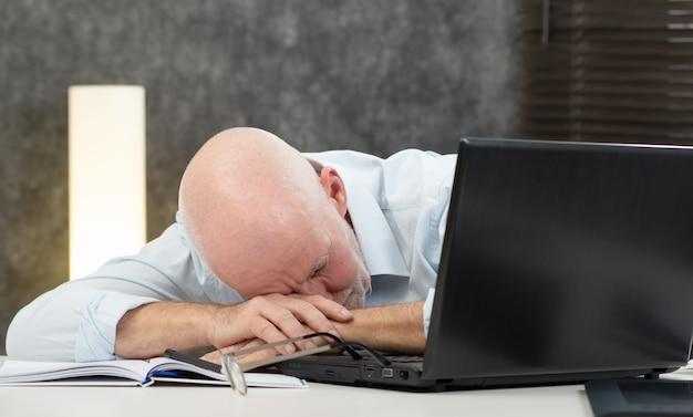 Homem de negócios sênior está cansado no escritório