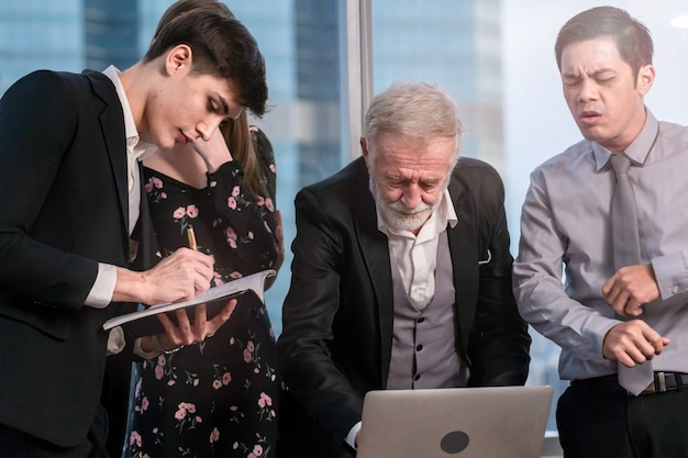 Homem de negócios sênior explicando questões de negócios para a equipe em uma sala de reuniões.
