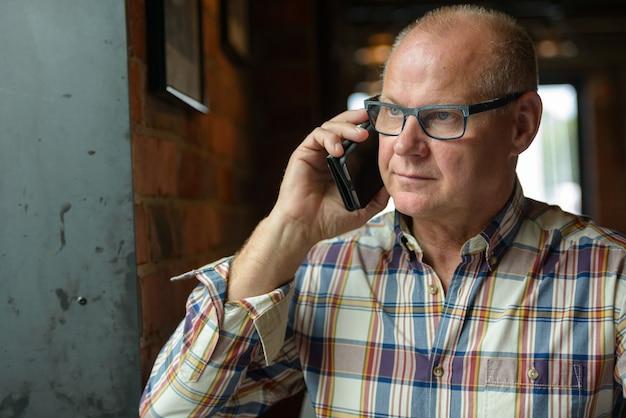 Homem de negócios sênior falando ao telefone na cafeteria