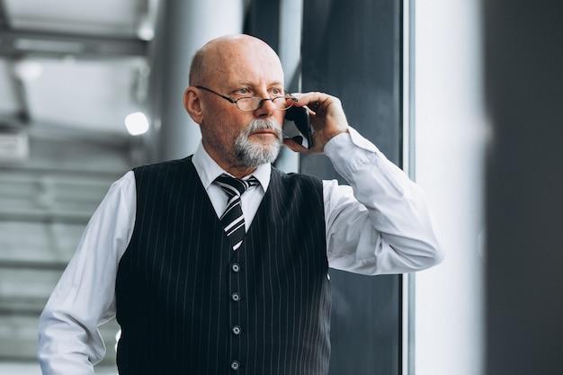 Homem de negócios sênior falando ao telefone no escritório