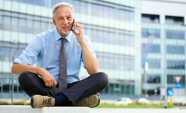 Homem de negócios sênior falando ao telefone, sentado em um banco ao ar livre em uma cidade