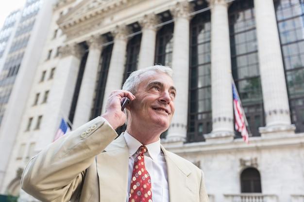 Homem de negócios sênior falando no celular em nova york