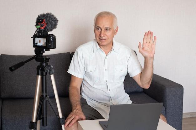 Homem de negócios sênior faz um vídeo para um blog em casa usando uma câmera de vídeo