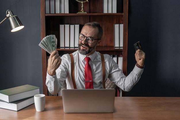 Homem de negócios sênior feliz segurando o monte de notas de dinheiro e cartão de crédito com o laptop na mesa