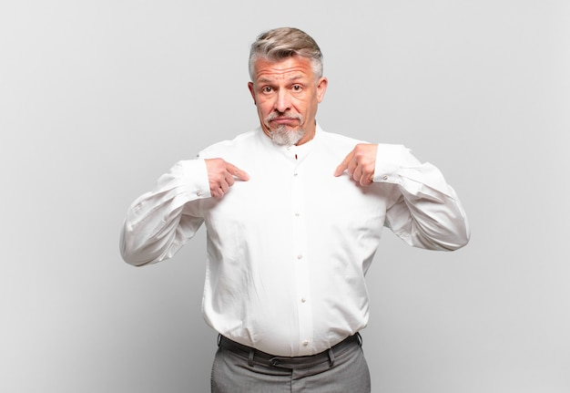 Homem de negócios sênior feliz, surpreso e orgulhoso, apontando para si mesmo com um olhar animado e surpreso