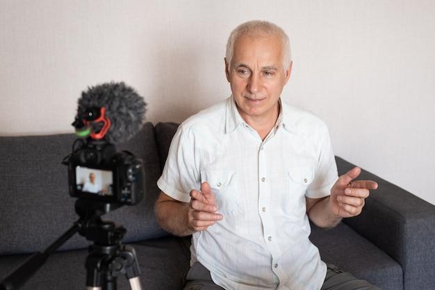 Homem de negócios sênior filmando um curso de treinamento online em casa usando uma câmera de vídeo