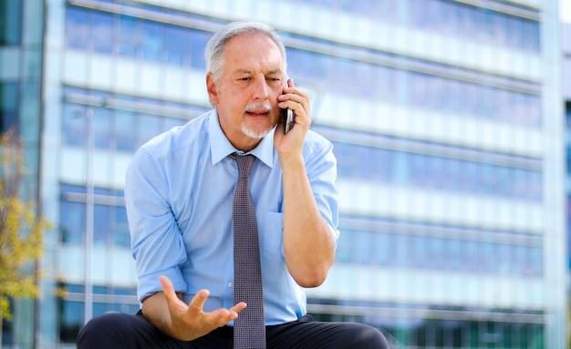 Homem de negócios sênior, gritando com o telefone ao ar livre, sentado em um banco