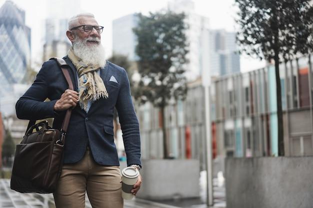 Homem de negócios sênior hippie andando com café para viagem ao ar livre em dia de inverno - foco no rosto