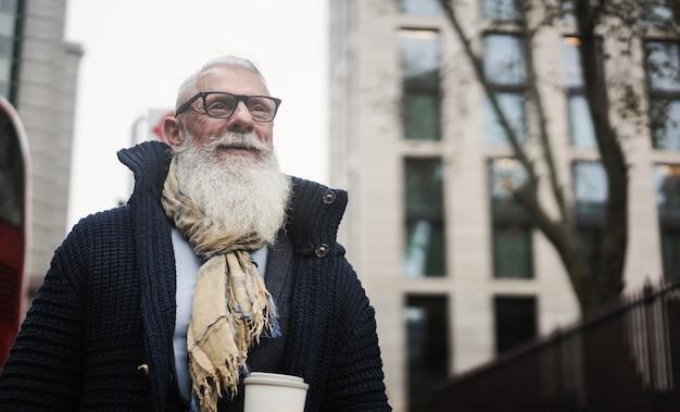 Homem de negócios sênior hippie bebendo café enquanto caminha para o escritório na cidade