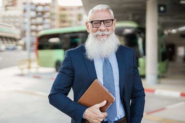Homem de negócios sênior hippie feliz esperando na estação de ônibus - foco no rosto
