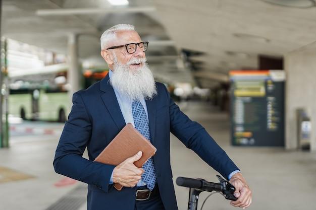 Homem de negócios sênior hippie segurando uma scooter elétrica enquanto espera na estação de ônibus - foco no rosto