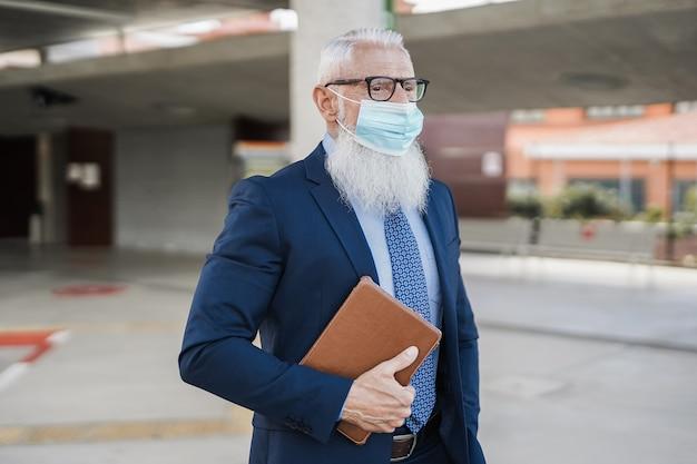 Homem de negócios sênior hippie usando máscara de segurança na estação de ônibus - foco no rosto