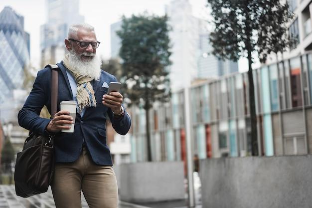 Homem de negócios sênior hippie usando o aplicativo para celular enquanto bebe café enquanto caminha para o trabalho - foco no rosto