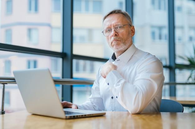Homem de negócios sênior, olhando para a câmera. último homem trabalhando com o laptop. bonito empresário de meia idade.
