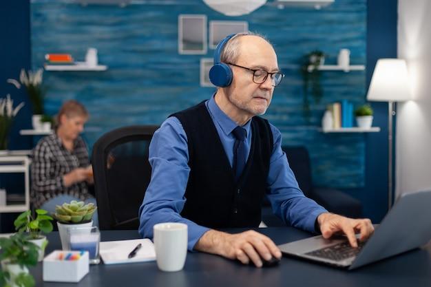 Homem de negócios sênior ouvindo música usando fones de ouvido e trabalhando em um laptop