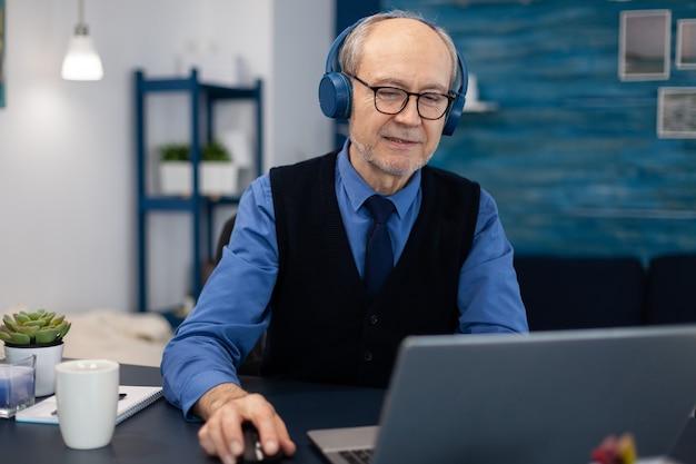 Homem de negócios sênior ouvindo música usando fones de ouvido