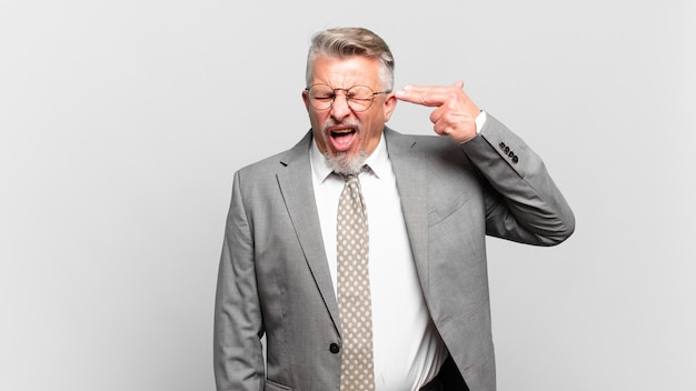 Homem de negócios sênior parecendo infeliz e estressado, gesto de suicídio fazendo sinal de arma com a mão, apontando para a cabeça