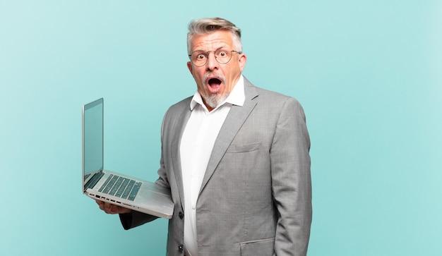 Homem de negócios sênior parecendo muito chocado ou surpreso, olhando com a boca aberta dizendo uau