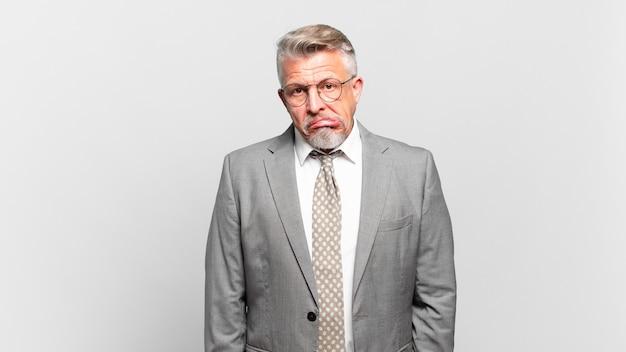 Homem de negócios sênior parecendo perplexo e confuso, mordendo o lábio com um gesto nervoso, sem saber a resposta para o problema