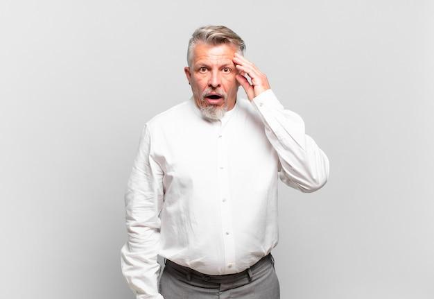 Homem de negócios sênior parecendo surpreso, boquiaberto, chocado, percebendo um novo pensamento, ideia ou conceito