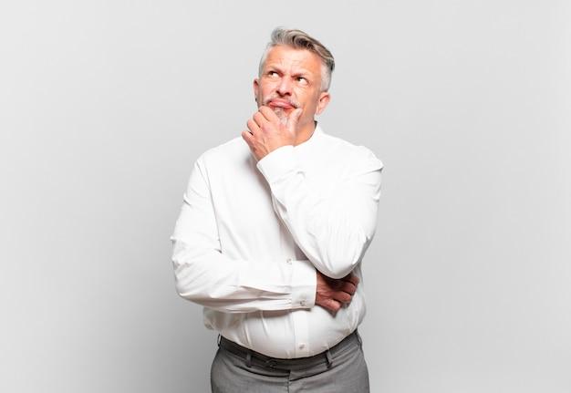 Homem de negócios sênior pensando, sentindo-se duvidoso e confuso, com opções diferentes, imaginando qual decisão tomar