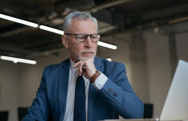 Homem de negócios sênior pensativo usando laptop