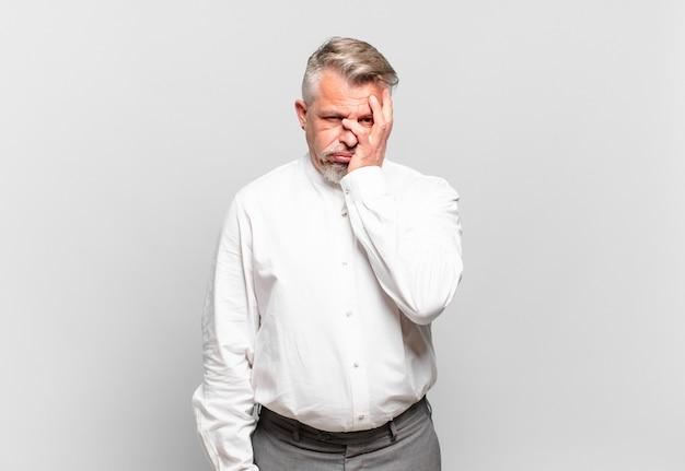 Homem de negócios sênior se sentindo entediado, frustrado e com sono após uma tarefa cansativa, enfadonha e tediosa, segurando o rosto com a mão