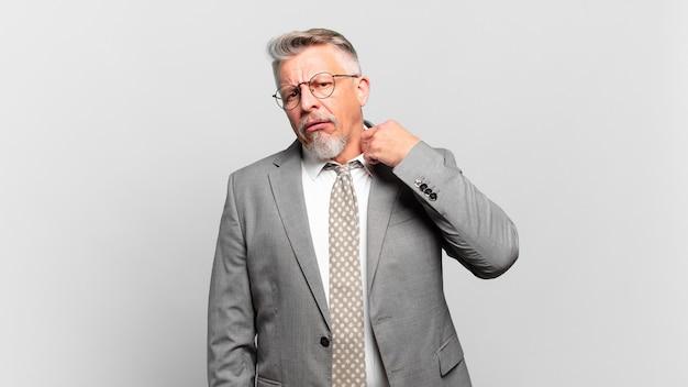 Homem de negócios sênior se sentindo estressado, ansioso, cansado e frustrado, puxando o pescoço da camisa, parecendo frustrado com o problema