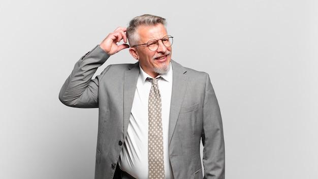 Homem de negócios sênior se sentindo perplexo e confuso, coçando a cabeça e olhando para o lado
