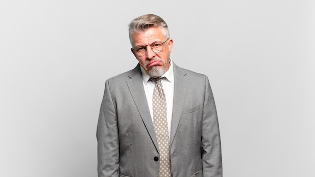 Homem de negócios sênior se sentindo perplexo e confuso, com uma expressão estúpida e atordoada olhando para algo inesperado