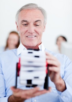 Homem de negócios sênior segurando um titular de cartão de visita